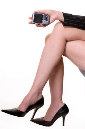 Bare legs of woman wearing sexy black high heel shoes sitting on a chair holding a cell phone over white