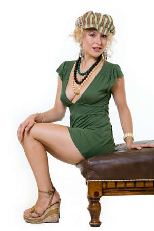 Full body of an attractive woman with curly blond hair in a sexy short green dress and accessories standing on white Reklamní fotografie