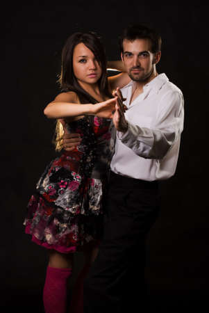fiance: Attractive Caucasian man and woman wearing dancing attire standing over black  Stock Photo