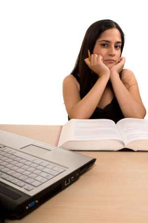 final thoughts: Young Hispanic woman sitting in front of desk with a pile of thick textbooks resting chin on hands with elbows on the table with laptop computer in front