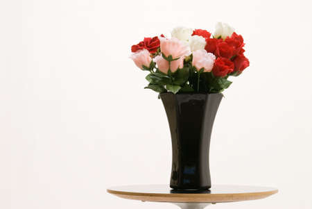 Redand Pink Roses In A Black Vase On Table Over White Stock Photo