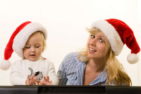 Adorable caucasian blond baby girl toddler sitting with mom both wearing Santa caps in front of a keyboard  photo