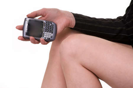 Close up of a woman's knees and hand holding a cellular telephone over white Stock Photo - 3871837