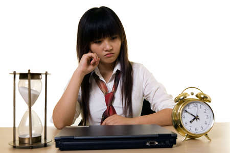 unifrom: Young Chinese girl wearing school uniform sitting at desk with hand on chin  with a pouting face expression with an alarm clock and hour glass