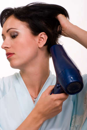 blow up: Attractive short hair brunette woman up close holding a blow dryer drying hair Stock Photo