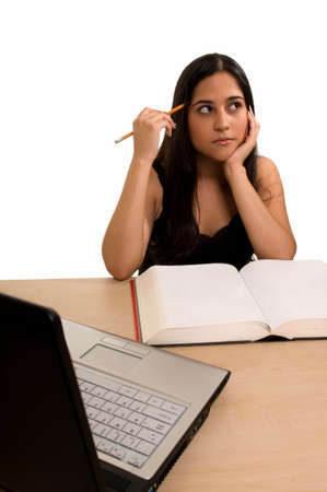 final thoughts: Young Hispanic woman sitting in front of desk reading a textbook holding a pencil to head with laptop computer in front