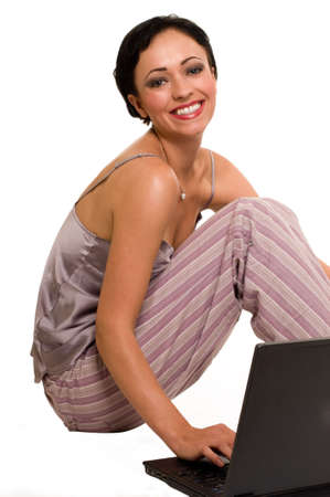 pjs: Attractive short hair brunette wearing pajamas sitting on white with laptop laughing expression Stock Photo