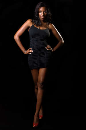 Full body of African American woman wearing short black dress over black background