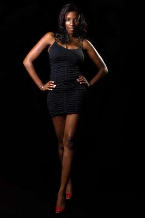 Volledige lichaam van African American vrouw draagt korte zwarte jurk op zwarte achtergrond