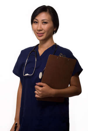 Young brunette asian woman health care worker wearing blue scrubs with chart in arms Фото со стока