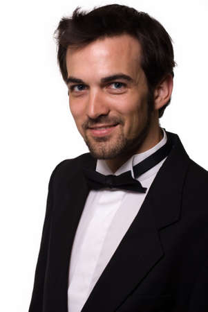 Attractive young brunette man with a beard wearing a black tuxedo