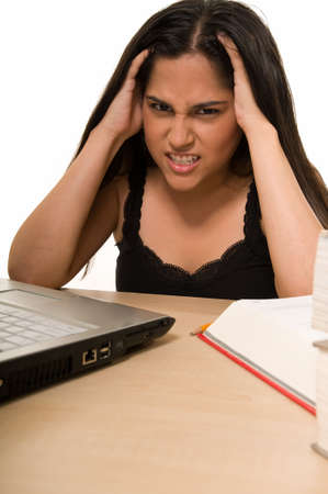 final thoughts: Young Hispanic woman sitting in front of desk looking at laptop computer with hands on head looking tired or frustrated