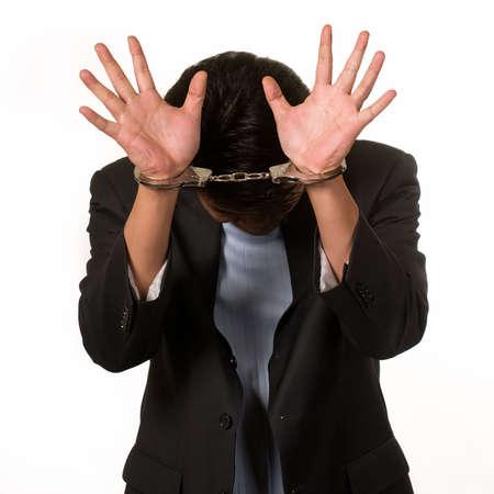 part prison: Brunette man in handcuffs hiding his face Stock Photo