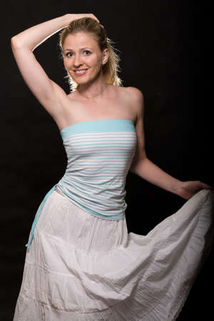 strapless: Attractive woman with blond hair wearing white skirt and strapless top standing over black Stock Photo