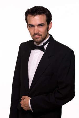 검은 턱시도 입고 수염을 가진 매력적인 젊은 갈색 머리 남자