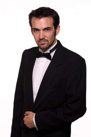 Attractive young brunette man with a beard wearing a black tuxedo photo
