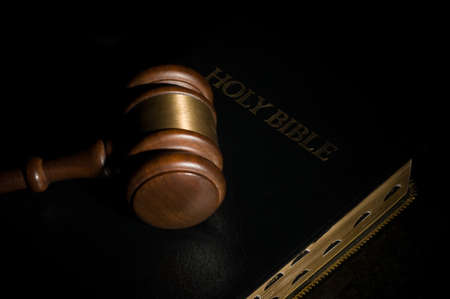 Judges gavel laying on top of a black holy Bible