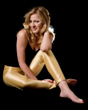 tight fit: Full body of a beautiful blond hair woman wearing sexy tight leather yellow pants and black top sitting on black
