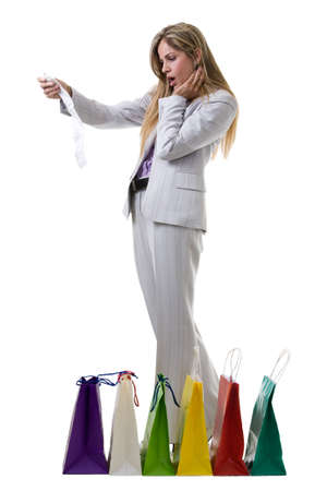 Attractive blond woman wearing grey business pant suit standing in front of a bunch of colorful shopping bags checking over the receipt