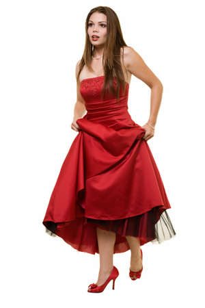 formal attire: Full body of an attractive young brunette woman wearing a long formal red satin gown holding up showing cute red shoes