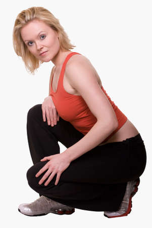 squatting down: Full body of an attractive blond hair woman in red and black workout attire squatting down on white background