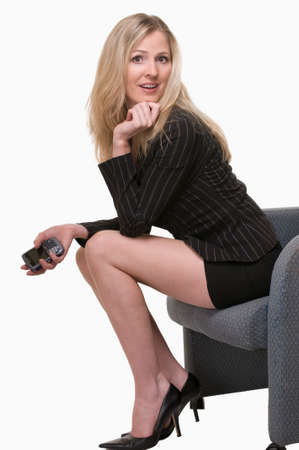 formalwear: Attractive blond woman wearing business suit with skirt and long legs sitting holding a cell phone Stock Photo