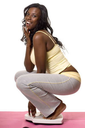 squatting down: Attractive African American woman squatting down on a bathroom scale with happy excited expression