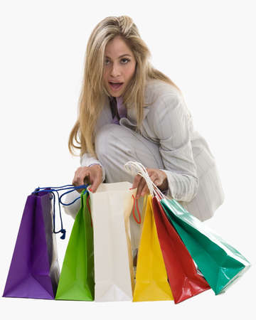 bending down: Attractive blond woman wearing grey business pant suit bending down and looking into colorful shopping bags with surprise expression