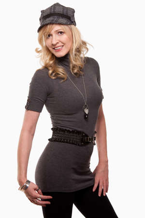 Attractive blond woman wearing long grey sweater with belt and black tights and hat standing over white background