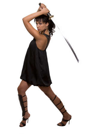 warrior pose: Full body of an attractive brunette woman wearing black dress holding samurai sword over head with serious expression over white