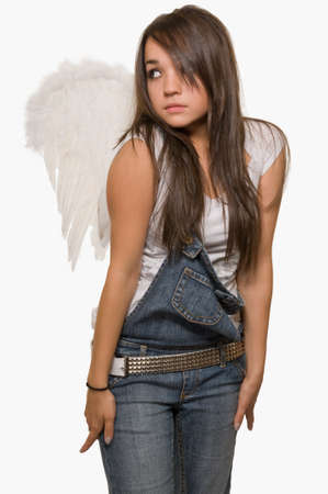 Young brunette woman wearing denim overalls wearing white angel wings standing over white
