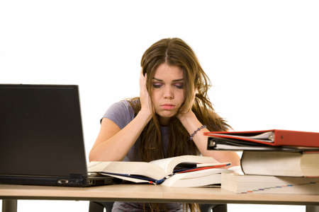 Young woman sitting at desk in front of laptop beside a pile of thick textbooks while reading with a frustrated stressed expression