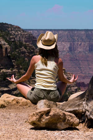 Woman in straw cowboy hat sitting doing yoga and meditating while looking out into the Grand Canyon