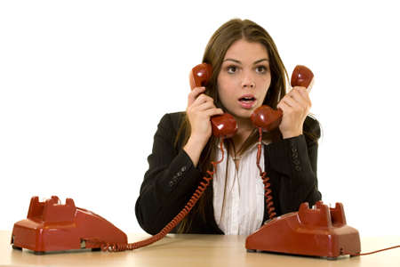 Brunette woman secretary sitting at desk with two red retro rotary telephone hand sets on ears looking overwhelmed photo