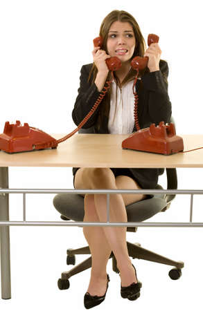 hot secretary: Brunette woman secretary sitting at desk with two red retro rotary telephone hand sets on ears looking overwhelmed