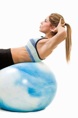 crunches: Attractive blond woman in great physical shape using a ball to do stomach crunches
