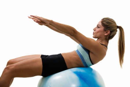 Attractive blond woman in great physical shape using a ball to do stomach crunches