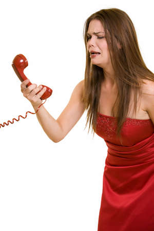 teary: Attractive young long hair brunette woman wearing a strapless formal red satin gown holding and looking at telephone receiver crying