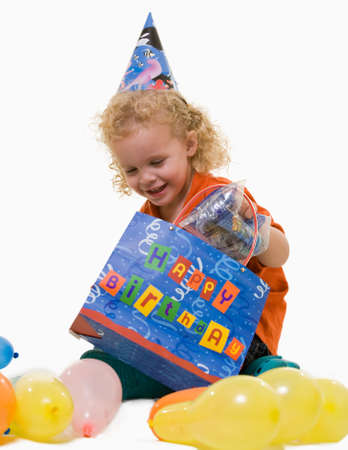Adorable little three year old boy wearing party hat sitting with balloons with hand in a gift bag photo