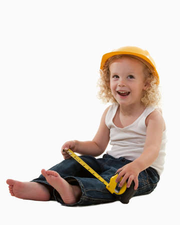 Cute young toddler with curly blond hair wearing construction worker hat, jeans and white tank top holding measuring tape over white smiling photo