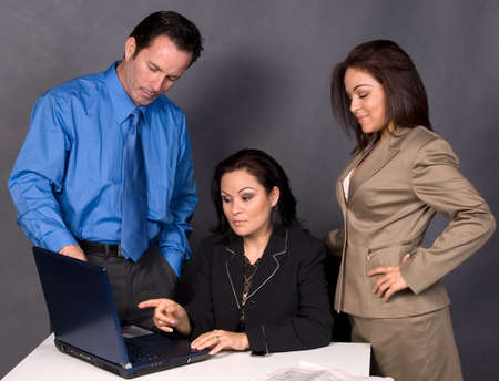 Three office workers, one man and two women standing around a desk in front of a computer having a discussion photo
