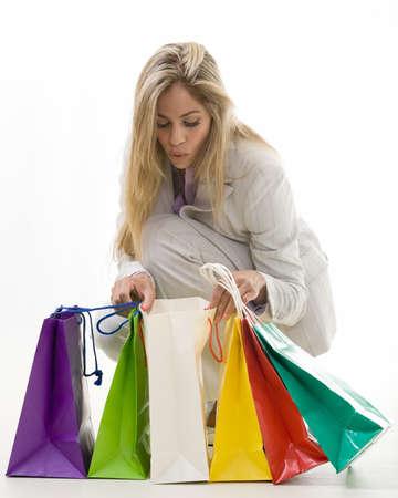 bending down: Atractiva mujer rubia llevaba traje pantal�n gris negocio de flexi�n hacia abajo y mirando hacia coloridas bolsas de la compra Foto de archivo