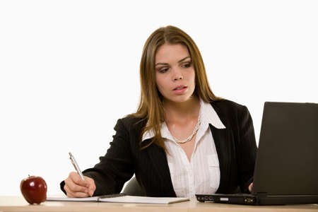 business attire teacher: Attractive young brunette woman in business suit writing on a notebook sitting at a desk and looking at a computer screen Stock Photo
