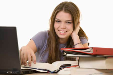 final thoughts: Young woman sitting in front of laptop beside a pile of thick textbooks while reading one with a content expression