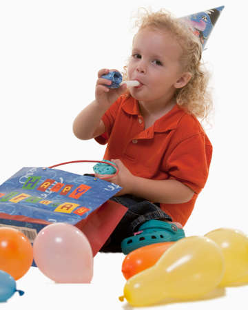 favor: Adorable little three year old boy wearing party hat sitting with balloons blowing on a party favor Stock Photo