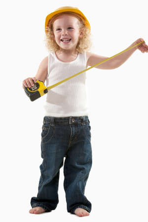 Portrait of an adorable little blond curly hair three year old boy wearing white muscle top and jeans and yellow hard hat dressed like a construction worker holding on to a measuring tape photo