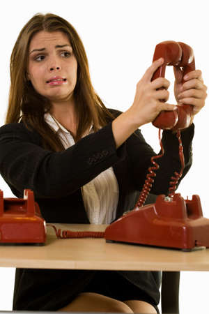 Close up of an attractive young brunette woman in business suit talking on an old style red phone while sitting at a desk and writing in a calendar photo