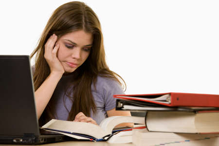 Young woman sitting in front of laptop beside a pile of thick textbooks while reading one with a frustrated stressed expression photo