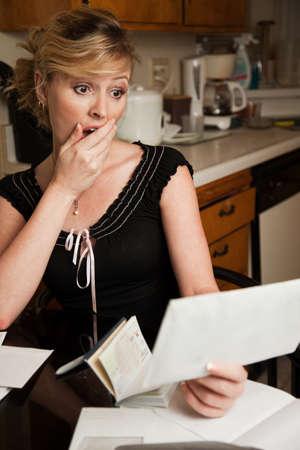 Blonde vrouw in casual kleding met de hand over de mond met geschokt meningsuiting terwijl kijken naar een utility bill