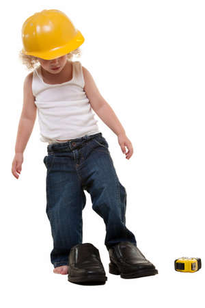 grown up: Adorable little blond curly hair three year old boy wearing white muscle top and jeans and yellow hard hat putting his feet into grown up mans shoes Stock Photo